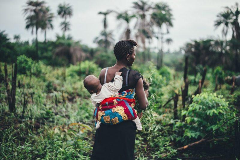 Nainen kantaa lastaan kantoliinassa selässään